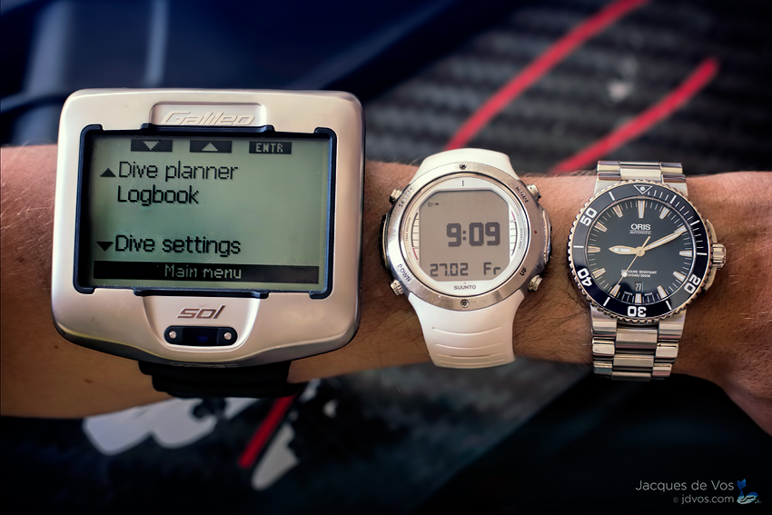 From left to right, ywo varients of a dive computer along with a standard analogue dive watch